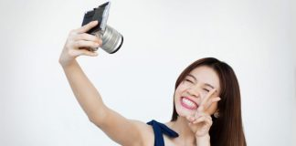 Happy asian woman smiling while taking selfie with mirrorless camera in front of white background