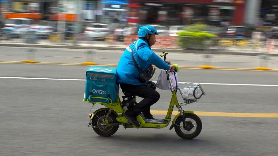 พนักงานขับรถส่งของเดลิเวอรี่บนแพลตฟอร์ม Ele.me Photo: Shutterstock