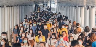 Crowds of Asian people wearing face protection while going to their workplace in Bangkok at morning rush hour